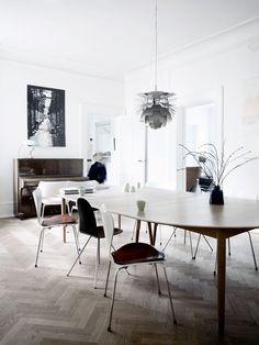 Spisestuens samlingspunkt er det lange bord omkranset af et udvalg af Arne Jacobsens klassiske stole 'Syveren' og 'Tungen'. 'Koglen' i loftet er en jubilæumsudgave i stål.