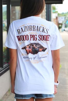 """Southern Trend: University of Arkansas t-shirt with a picture of the campus inside the Razorback on the back. White comfort color tee. Features front left chest design. Model is 5'9"""" pant size 2 weari"""