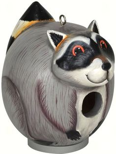 Raccoon Gord O Bird House. You and your friends will enjoy this cute raccoon bird house as much as your feathered friends. Even your hubby or boys will appreciate seeing him in your yard. This is one raccoon that it will be nice to have around. Bird house is hand crafted from renewable albesia wood, then hand painted using safe, non toxic paint, then a final coat of polyurethane to create a safe, long lasting bird house. Comes with clean out door. 7.5 x 5.5 x 8.5 inches high.
