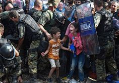 Children cry as people try to push past riot police at the Macedonian border. Syria refugees.