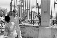 A Dominican army guard at the National Palace is photographed the instant he shoots and kills a high school student (arms raised) protesting U.S. Army presence in Santo Domingo, Dominican Republic, on September 27, 1965. In April of 1965, the United States occupied the Dominican Republic during the Dominican Civil War, holding it for more than a year.  Photo credit: Jim Bourdier / AP