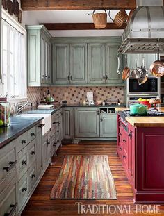 This colorful kitchen has cabinets painted soft green and an island base painted bold red. - Traditional Home ® / Photo: Emily Minton Redfield  / Design: Dawn Bergan