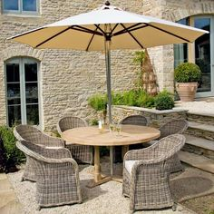 Turnberry South American oak table, £905; Antibes parasol, £300; Pesaro wicker chairs, £220 each,  all Neptune.