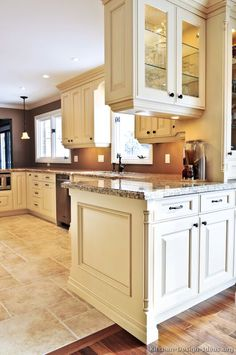 Traditional Antique White Kitchen Cabinets + brown wall color cabinet color and under counter lighting floor tile