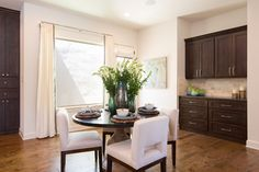Enjoy breakfast bathed in light.  Turquoise, green and brown accents play off the airy cream tones, with the rich dark wood cabinetry framing the breakfast area and blending it into the kitchen.