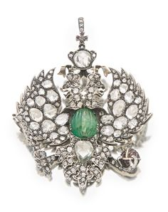 The Princes Shcherbatov: A Russian emerald- and diamond-set double-headed eagle pendant, circa 1880, the silver and gold mounts formed as the double-headed Imperial eagle, set with rose cut diamonds, the crown with a cushion cut diamond, the body set with a fluted oval cabochon emerald, the central cross on the crown and the orb set with rubies, with diamond-set suspension ring, the reverse of the crown set with riband carrier. Provenance: Prince Kyril Scherbatow, Princess Lucile Scherbatow.