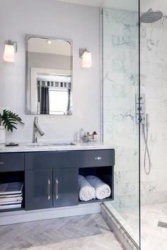 Simple yet chic white and black bathroom donning marble herringbone bathroom floor tiles showcases a gorgeous…