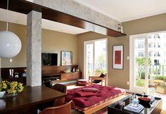 Para contrastar com a parede na cor concreto, o arquiteto Gustavo Calazans descascou os pilares e a viga central e acrescentou prateleiras de imbuia na sala deste apartamento