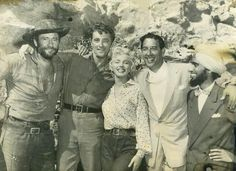 """Murvyn Vye, Robert Mitchum, Marilyn Monroe and others on the set of """"The River of No Return"""" (1954)."""