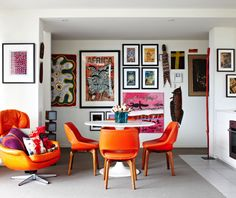 Orange chairs sit in front of an amazing art wall