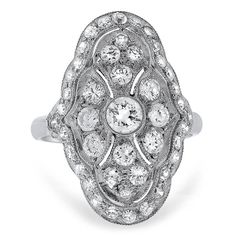 A sparkling round brilliant diamond sits at the center of this glamorous platinum ring from the Art Deco era.