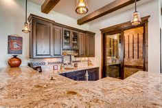 Full wet bar with granite counter tops and dark walnut cabinets. Also boasts exposed wood beams in the ceiling and wine cellar