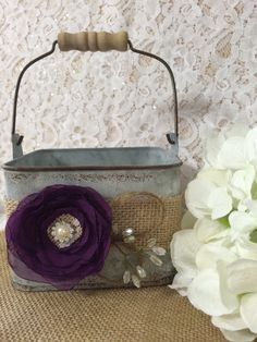 This charming flower girl bucket will be the perfect finishing touch to your rustic, outdoor, beach, country, shabby chic, vintage style or barn wedding. This flower girl galvanized bucket is decorated with burlap ribbon, handmade chiffon flower (shown in # 40/plum purple), jute, wire beaded accent, and is finished with a lace burlap center and pearl/rhinestone brooch. Bucket measures 5x5x3.5 Dont see what youre looking for ? I would love to custom make a one of a kind piece for you. All…