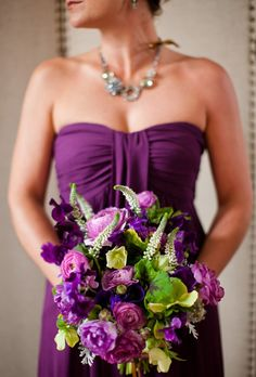 Dress up a plum bridesmaid's gown with a bouquet with various purple shades from a light lilac to a dark plum: ranunculi, sweet peas, dusty miller, veronica, hellebores and scented geranium leaves.