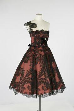 Owen Hyde Worth burgundy strapless satin taffeta dress with lace overlay, velveteen ribbon, and diamond brooch. Circa 1955.