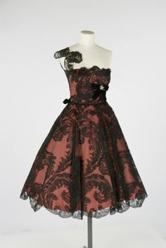 Owen Hyde Worth burgundy strapless satin taffeta dress with lace overlay, velveteen ribbon, and diamond brooch. Circa 1955.