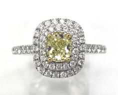 Ladies 18kt white and yellow gold diamond ring. Ring is set with 1 GIA graded radiant cut natural yellow diamond weighing .74ct. Also set in mounting are 54 brilliant round cut white diamonds weighing .50ct. A total of approximately 1.24ct.