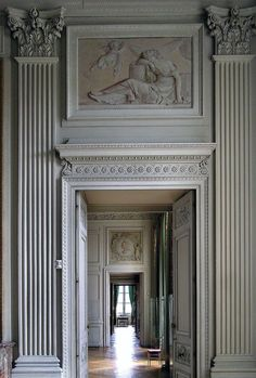 Compiegne Castle, Picardy, France.  fluted pilasters with Corinthian capitals flanking the doorway, romantic frieze, and grey paint thorughout.