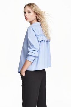 Wide blouse with a frill: Wide, long-sleeved blouse in cotton poplin with a decorative frill trim at the back, a chest pocket, buttons down the front and a gently rounded hem.