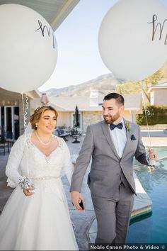 Bride and groom holding white 'Mr & Mrs' balloons, couple photography ideas