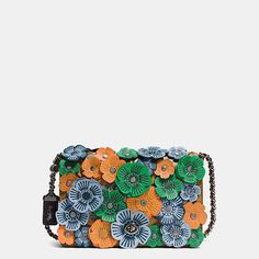 Luxury craftsmanship meets the whimsicality of hand-placed leather blooms on a charming silhouette that reimagines a beloved Coach design from the 1970s. The bag is crafted in modern glovetanned cowhide with an iconic turnlock and a chain strap woven thro