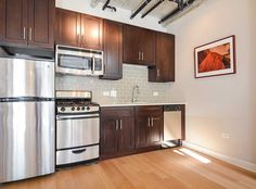 The model kitchen of our live/work units at AMLI Evanston, luxury Evanston apartment rentals, featuring stainless steel appliances and elegant granite countertops