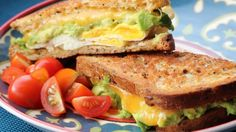 Swiss cheese, fried egg, Cheddar cheese, fried egg, and avocado are layered between toasted bread in this filling avocado breakfast sandwich.