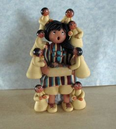 The Storyteller originated in 1964 by a Native American Pueblo woman when she created a figure of an adult with many surrounding children, representing the value of storytelling for children to learn the customs and legends of the people. This motif has become very popular. This adorable Storyteller figure is sitting on a rock with 9 wide-eyed, some open-mouthed children surrounding her (including one baby in a papoose). She is dressed in a ecru colored dress with flowing sleeves, overlaid…