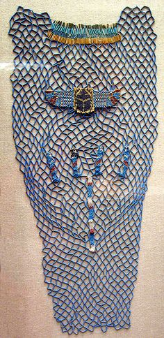 "680-670 BCE  Constructed of tubular faience beads strung together in a net pattern, this shroud was sewn onto the outer wrappings of Tabakenkhonsu's mummy. Additional beads in various colors have been worked into the garment at several points: a beaded broad collar has been added to the top, where the garment came over the mummy's neck; over her breast was a winged scarab to protect the heart; and on the abdomen are the four ""canopic"" genii who guarded the viscera."