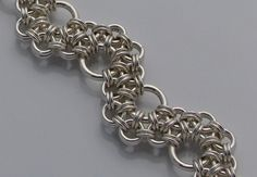 This bracelet is made to order. Please allow 7-10 days for delivery. This bracelet features sterling silver handcut rings in three different ring sizes. Featuring nearly over 250 rings, this bracelet is surprisingly lightweight. The bracelet is woven in a chainmaille pattern known as stepping stones which was created by CorvusRedcrow. A unique bracelet, it is finished with a sterling silver flower toggle. This item has been tumble polished for unbelievable shine and strength. Please indicate…