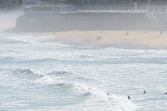 What to do and see in #Biarritz: the main beach. People walking in the mist on Grande Plage of Biarritz