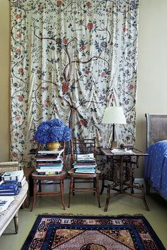 In a guest bedroom, a Palamur coverlet from the 1700s on the wall behind faux-bamboo chairs and a table.