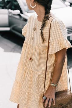 This yellow gingham number is the perfect summer dress! We'd pair it with simple gold hoop earrings and crochet slingback heels.
