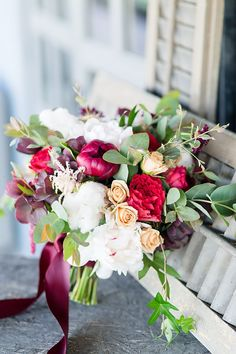 Arranged by Petals Couture, the bridal bouquet featured 'Buckeye Belle' peonies, 'Festiva Maxima' peonies, 'Wanted' garden roses, spray roses, scabiosas, hellebores, cotton bolls, love-lies-bleeding, and greenery tied with a shiny satin ribbon. | Photo by Rebecca Ellison