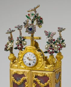 Miniature secretary incorporating a watch. Bejeweled butterflies and flowers that tremble in the slightest breath of air adorn this whimsical object, which plays tunes on a hidden music box and incidentally tells the time. The spring mechanism that powers the music is wound by inserting a key into a hole hidden behind one of rosettes near the bulls that support the cabinet