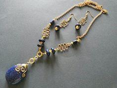 Collana con elementi e ciondolo in lapislazzuli, montata con catena e componenti in metallo color oro. Orecchini con lapislazzuli e componenti in metallo color oro. Realizzazione artigianale.