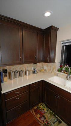 StarMark maple mocha cabinets with Caesarstone buttermilk countertop and stone backsplash.