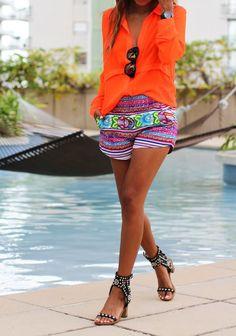 Comprar ropa de este look: https://lookastic.es/moda-mujer/looks/blusa-de-botones-pantalones-cortos-sandalias-de-tacon-gafas-de-sol-reloj/12379 — Reloj de Cuero Negro — Gafas de Sol Negras — Pantalones Cortos de Flores Multicolor — Blusa de Botones Naranja — Sandalias de Tacón de Cuero con Tachuelas Negras