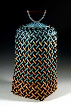 Maggie Henton -Untitled 1991.  Wood, metal, and plastic. The colors in this basket gradually change from orange to turquoise and are made brighter in contrast to the black cane with which they are woven. In order to achieve this intensity of color, many layers of dye and paint have been applied to the cane weave
