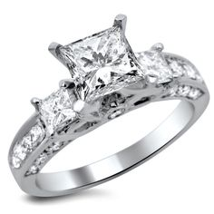 Three large princess cut center white diamonds in a prong setting add sparkle to this three-stone engagement ring surrounded by side stones. Highly polished 14k white gold with several round and princ