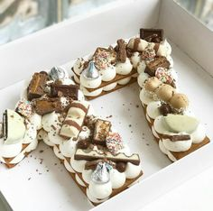 Cookies layered with cream and decorated with chocolates, brownie bites, meringue & macaroons