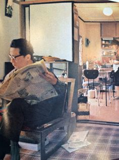 Tokyo 1964. Man reads newspaper while wife cooks.