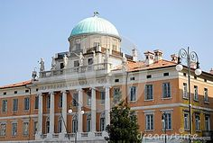 Photo made an important and historic building in Trieste in Friuli Venezia Giulia (Italy). In the image of the building, there are two floors of the central part of the facade, rich in six columns and six statues on top over balausta front of the dome which takes us into the blue sky. In the right foreground is seen a lamppost and a small tree.