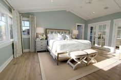 Steely light blue bedroom walls, wide-plank rustic wood floors, patterned curtains, lots of light, vaulted planked ceiling.