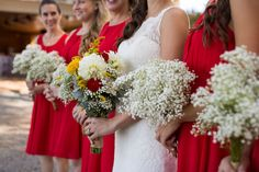 Maybe baby's breath for the bridesmaids and guys boutonnieres?  Would be more striking against the black than this red.