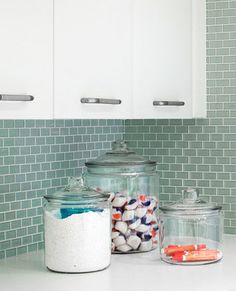 Make your laundry room pretty. Oversized canisters and jars stylishly hold powder detergents, dryer sheets, clothespins, and more.