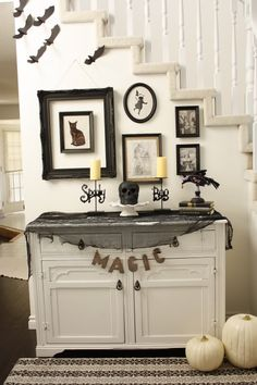 Halloween entryway with tea-stained printed art in frames.
