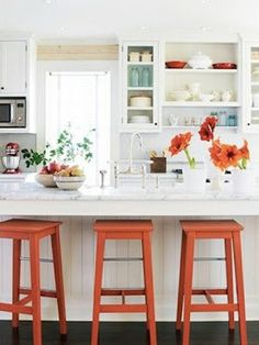 Fun bright bar stools in an all white kitchen...love!