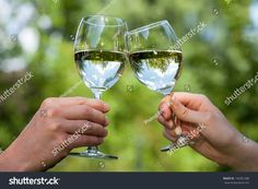 Two people clinking each other's glasses with water