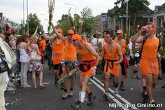 """Vierdaagse van Nijmegen, finalists arriving at the """"Via Gladiola"""". A Dutch saying goes: de dood of de gladiolen (=death or the gladiola's)"""